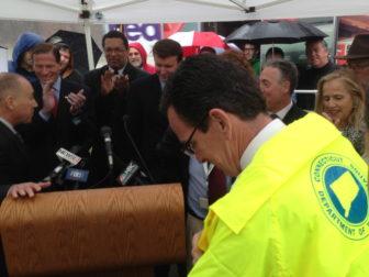 Gov. Dannel P. Malloy slips on a DOT rain slicker Tuesday.