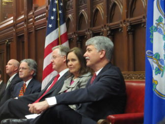 After a handshake, Sharkey and Williams take their seats, separated by Secretary of the State Denise Merrill.