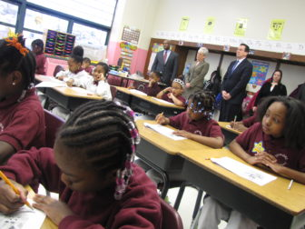 Jumoke Academy charter school students work on an assignment while Gov. Dannel P. Malloy and Lt. Gov. Nancy Wyman watch in the back.