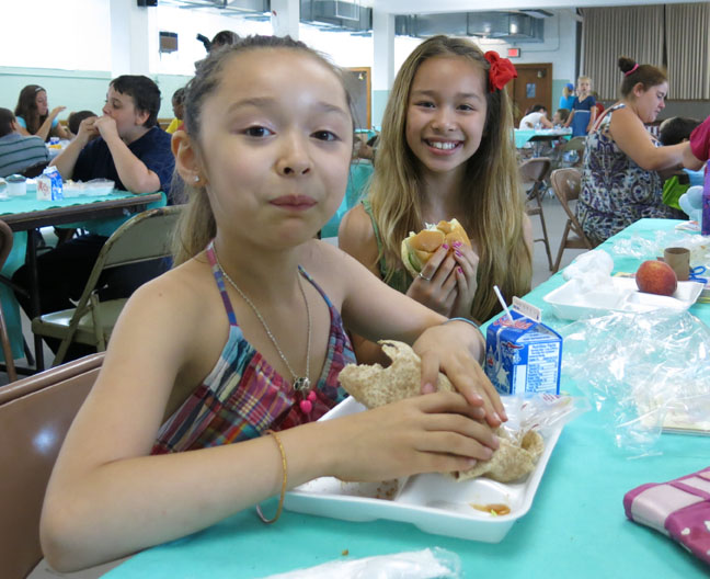 Maysalee Gray-Khen (left), 7, and Monysohn Gray-Khen (right), 9, enjoy their lunch at Ellington's Summer Meal program, at St. Joseph's Church.