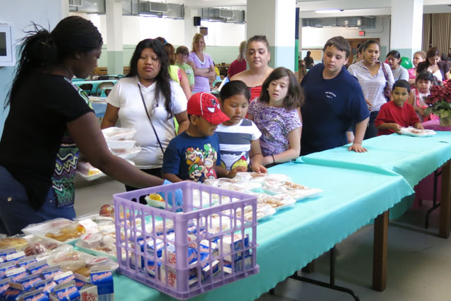 Children and their parents line up to receive meals.