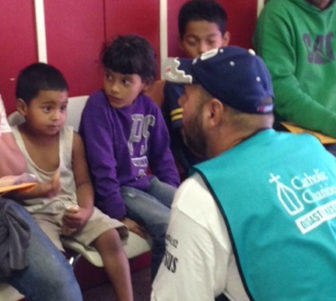 A Catholic Charities representative interviews migrant children at a holding station.