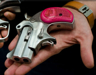A Bond Arms pink- gripped double-barrel derringer.