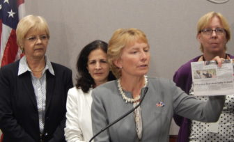 Rep. Pam Sawyer (foreground) shows headline about infant death in EH. Reps. Tami Zawistowski and Gail Lavielle and Sen. Cathy Osten (L to R) in background.