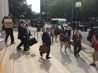 Rowland's legal team leaving court earlier in trial. At center is Reid H. Weingarten.