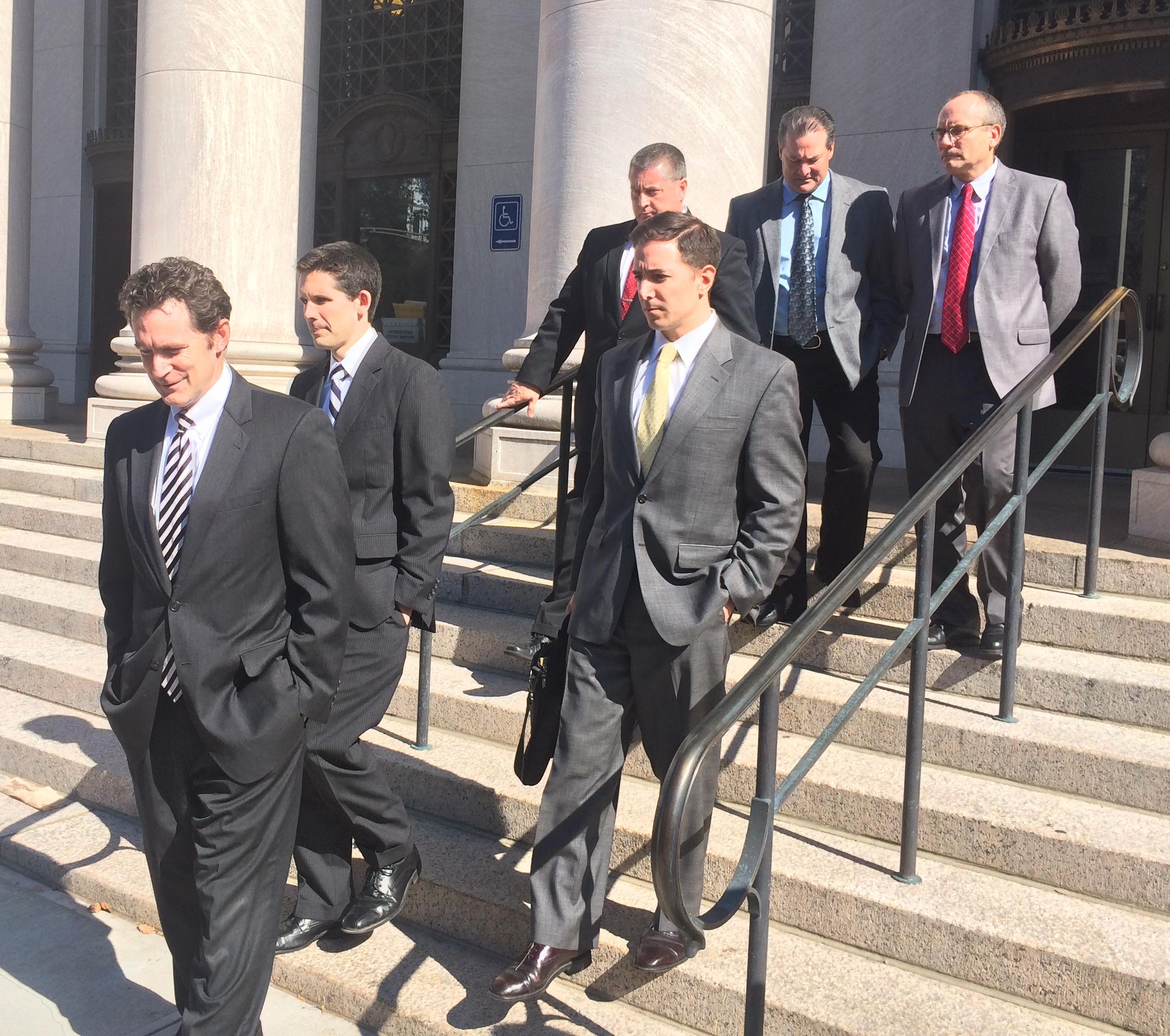 Michael J. Gustafon, trailed by Liam Brennan, Christopher Mattei and investigators.
