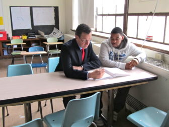 Gov. Malloy works with a student in a school in Norwalk earlier this year