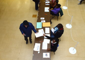 A voter at Hartford Public Library gets his ballot. This was one of several locations that had a delay in getting the voter list.