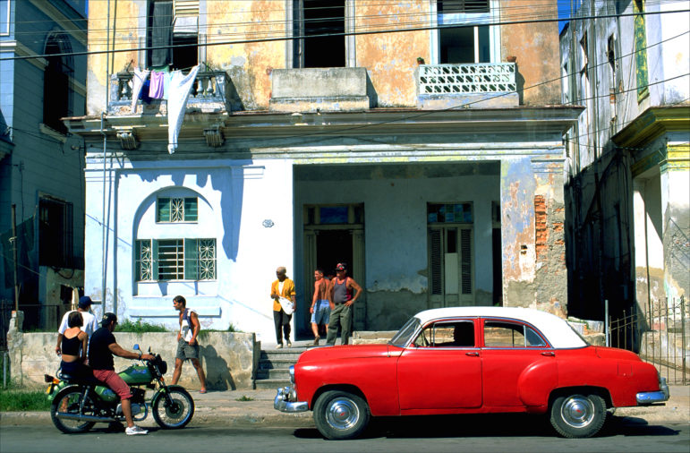 A vintage early 1950s Chevrolet adds some color to an otherwise drab, crumbling apartment building in Havana's Vedado neighborhood.