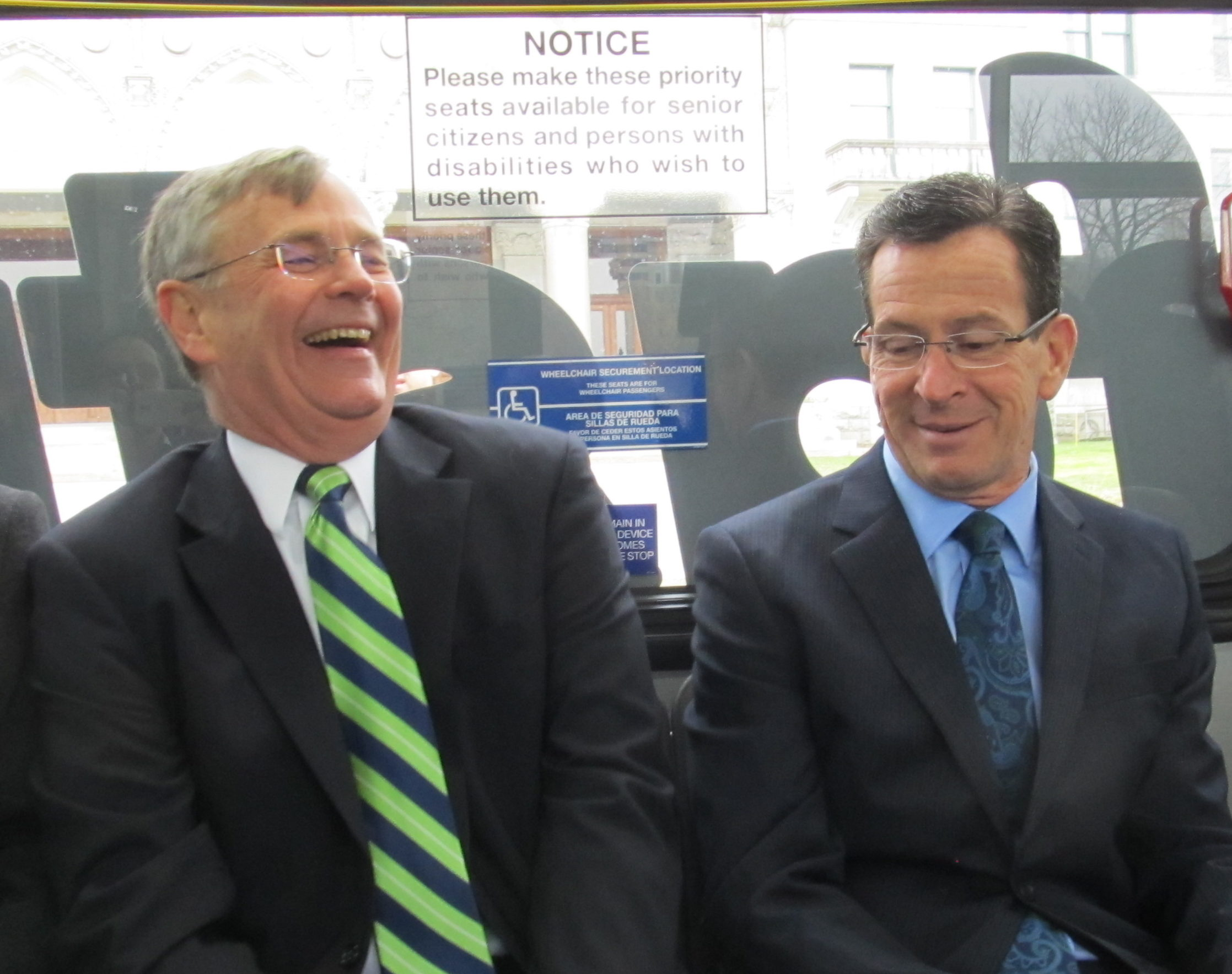 Gov. Dannel P. Malloy and  Transportation Commissioner James Redeker share a laugh at the start of a CT fastrak tour. How to fund transportation was not the source of their amusement.
