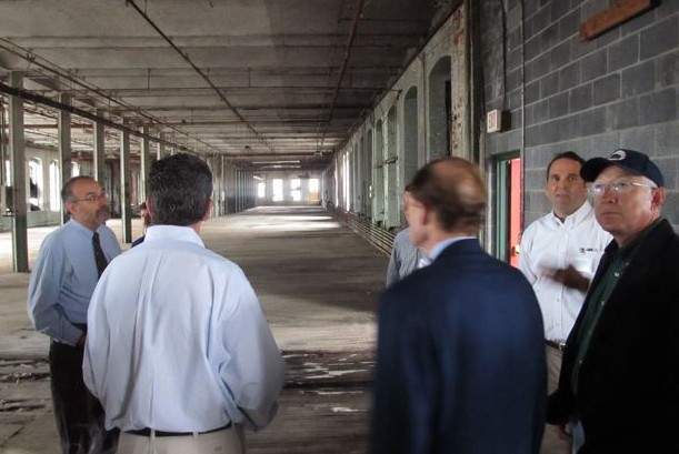 Gov. Dannel P. Malloy, Connecticut U.S. Sen. Richard Blumenthal, backs to camera, and then-U.S. Interior Secretary Ken Salazar, left, on a tour of the Colt Armory with developers in September 2011.