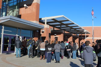 Parents wait with their children for a school choice fair in Southwest Hartford