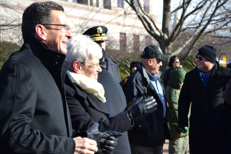 Gov. Dannell P. Malloy and Lt. Gov. Nancy Wyman watch the inaugural parade pass the Legislative Office Building.