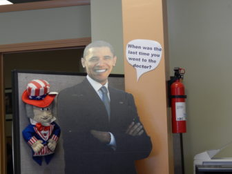 """When was the last time you went to the doctor?"" a speech bubble next to a cardboard cutout of the president read inside a Hartford insurance and tax office that advertised helping people sign up for Obamacare."