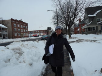 Marta Persia walks down Wethersfield Avenue in Hartford, hoping to find people who are uninsured and hang up flyers advertising help getting coverage.