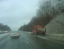 A Connecticut DOT truck plowing and treating a highway.