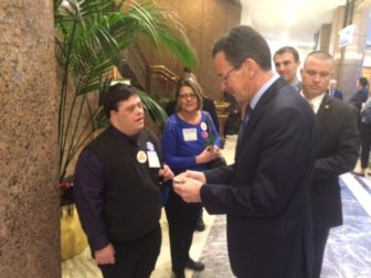 Zeb Olko gives Gov. Dannel P. Malloy his card. Olko, who has an intellectual disability,  was the Legislatie Office Building to ask that funding be restored to the Department of Developmental Services.
