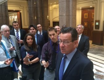 Gov. Dannel P. Malloy talks to reporters about transportation funding. At right is Commissioner James P. Redeker.