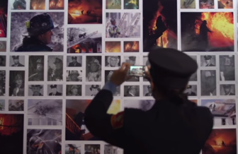 A Boston firefighter photographs a memorial to colleagues  who died from cancer.