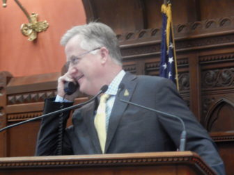 Speaker Brendan Sharkey on the phone from the House podium as the chamber debates budget adjustments late Monday.