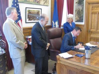 Gov. Dannel P. Malloy signs the budget. From left, House Speaker J. Brendan Sharkey, Senate President Pro Tem Martin M. Looney and Lt. Gov. Nancy Wyman.