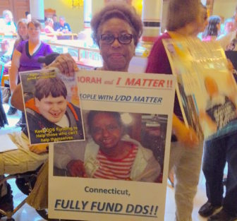 Velma Williams-Estes of Meriden holds a picture of her intellectually disabled daughter Deborah while urging lawmakers Tuesday not to make further cuts to social services in the new state budget.