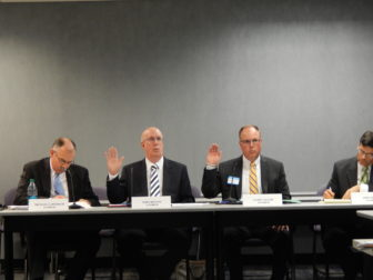 Anthem officials John Bryson, left, and James Augur are sworn in during the rate hearing.