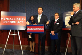 Sen. Chris Murphy, at podium, with Sen. Bill Cassidy, right, and Mary Gilberti at rear.