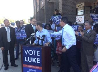 Gov. Dannel P. Malloy reaches behind Luke Bronin to congratulate a member of Bronin's slate.