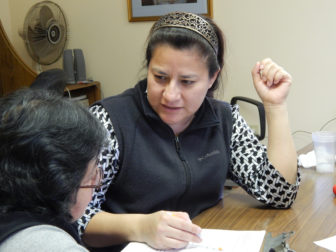 Volunteer Maria Hernandez helps a woman sign up for health care insurance during an event in Windham.