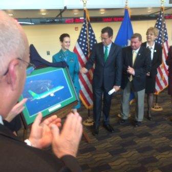 Gov. Dannel P. Malloy watches as Aer Lingues flight attendants unveil a photo marking the airline's symbolic arrival