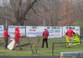 Protesters hang signs along the route regents will walk to get to their monthly meeting.