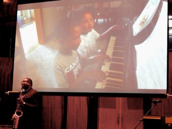 A video of Ana Grace and Isaiah Márquez-Greene playing piano and singing played at the beginning of the conference after their father, musician and professor Jimmy Greene, played.