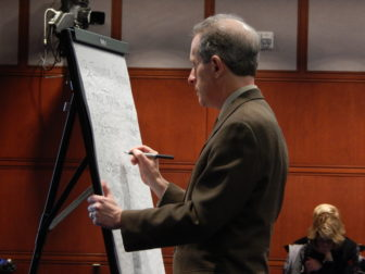 Consultant Michael Bailit takes notes as members of the health care cabinet talk about the study.