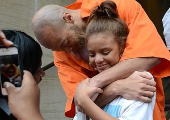 Sean Adams, free after 17 years, hugs the daughter born after his arrest.