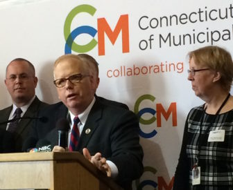 Danbury Mayor Mark Boughton, president of the Connecticut Conference of Municipalities, at podium, is flanked by Seymour First Selectman Kurt Miller and Sprague First Selectman Cathy Osten, who also is a state senator.