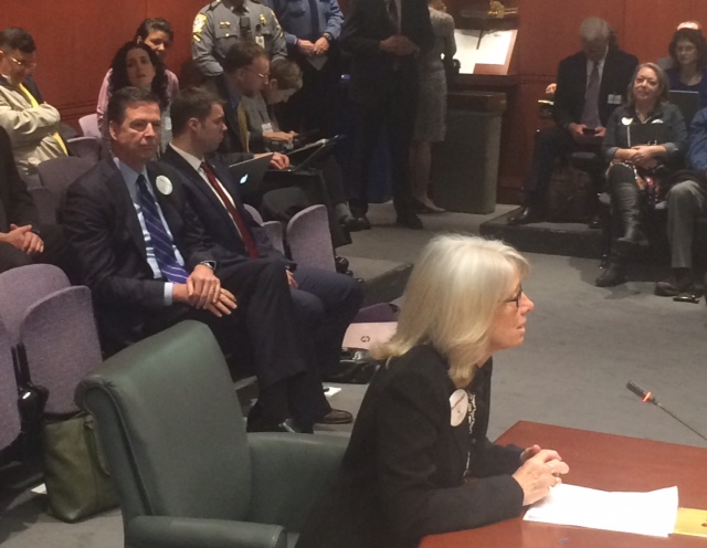 FBI director James B. Comey watches his wife, Patrice, testify in Hartford.