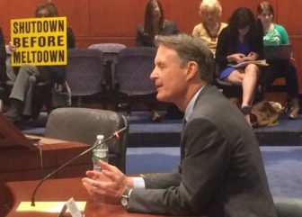 Evan Bayh, the co-chair of an advocacy group funded by the nuclear power industry, makes a pitch for the importance of nuclear power. A spectator demurs.