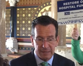 Gov. Dannel P. Malloy speaks to reporters as advocates argue to shield hospitals from budget cuts.