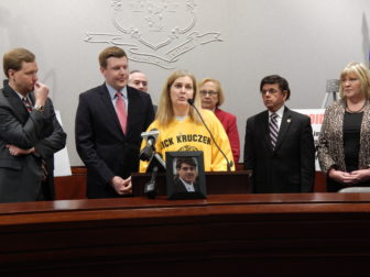 Sue Kruczek, wearing her son Nick's memorial hockey jersey, speaks in favor of a bill to cap the supply of opioid prescriptions. Nick died at age 20 of a heroin overdose after initially taking prescription opioids.