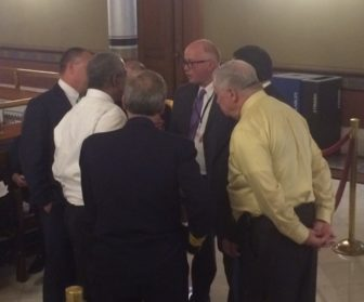 Rick Hart, center, huddling with firefighters and others over a last-minute glitch.
