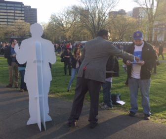 The Rev. John Henry Scott III and a cutout of Bernie Sanders reach out to potential volunteers.