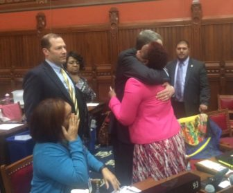 Rep. Robyn Porter, a victim of domestic violence, is hugged by a colleague, Brian Becker, after passage of a domestic violence bill she championed.