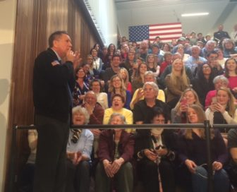 John Kasich shushes the crowd as he sneaks up on Chris Shays.