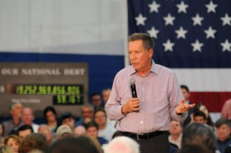 Republican presidential candidate John Kasich speaks at Glastonbury High School Friday with his traveling national debt clock running behind him.
