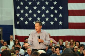 Republican presidential candidate John Kasich addresses a crowd of about 1,300 at Glastonbury High School.