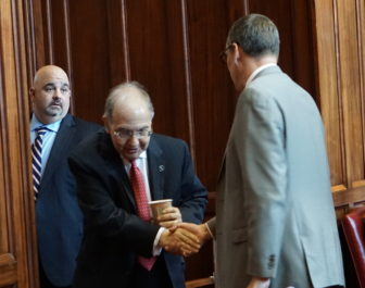Budget chief Ben Barnes, right, shakes hands with the Senate leader, Martin Looney as debate begins. At Watching is Looney's top aide, Vinnie Mauro.
