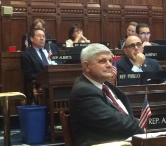 Retiring Reps. Bill Aman, foreground, and Mike Alberts, watching a video tribute.