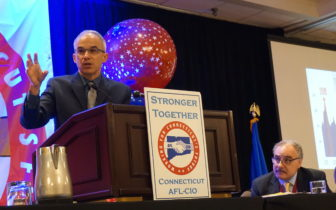 Ian Haney Lopez speaks to labor delegates in Hartford. At right, Sal Luciano of AFSCME listens.