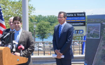 Traffic passes behind him on Route 9 as Gov. Dannel P. Malloy waits to be introduced by Mayor Dan Drew.